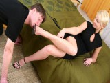 Lovely young boy kneels down in front of his mistress's couch and teases her feet with his playful tongue